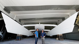 Jerome Delafosse and Victorien Erussard stand in front of the Energy Observer catamaran which is being given finishing touches in Saint Malo.