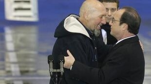 Serge Lazarevic (L) is greeted by French President François Hollande on his return to France this week