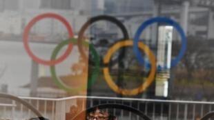 Les anneaux olympiques se réflétant sur une vitrine dans le parc de bord de mer d'Odaiba (baie de Tokyo) et un Japonais se protégeant du nouveau coronavirus avec un masque, le 8 mars 2020