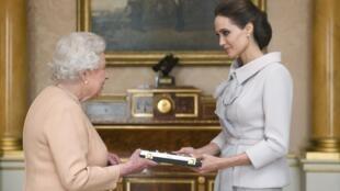 A rainha Elizabeth II condecora a atriz Angelina Jolie.