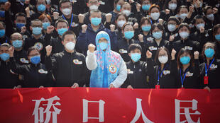 Un equipo de asistencia médica de la provincia china de Jiangsu grita consignas en Wuhan el 19 de marzo de 2020, antes de partir tras haber ayudado a combatir el coronavirus COVID-19