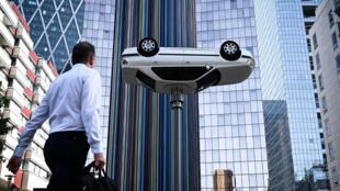 Un homme passe devant une installation artistique de Benedetto Bufalino intitulée «La voiture sur le lampadaire», lors de l'exposition d'art contemporain «Les Extatiques», tenue en plein air à La Défense à Nanterre près de Paris, le 28 juin 2019.