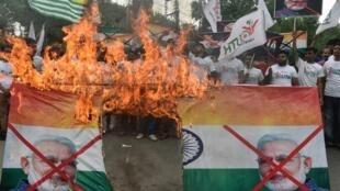 Des militants du groupe Forum de la jeunesse du Cachemire crient des slogans en brûlant une photo du Premier ministre indien Narendra Modi et du drapeau indien lors d'une manifestation à Lahore, le 15 août 2019.