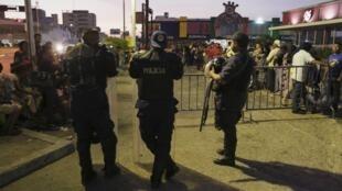 Cảnh sát giữ trật tự trong lúc người dân xếp hàng đợi siêu thị mở cửa ở Venezuela, 08/08/2015.
