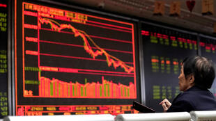 An investor watches a board showing stock information at a brokerage office in Beijing, China October 8, 2018.