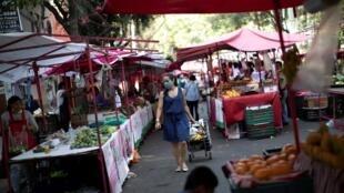 Des maraîchers maintiennent leurs stands dans un marché de Mexico, le 31 mars 2020 pendant la pandémie de Coronavirus.