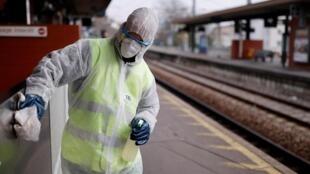 Un travailleur nettoie la gare avec un désinfectant pour ralentir la propagation du coronavirus à Suresnes, en banlieue de Paris.