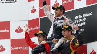 El piloto venezolano Pastor Maldonado celebra su triunfo en el Gran Premio de España, el domingo 13 de mayo de 2012, al imponerse por delante a Fernando Alonso (izq.) y Kimi Raikkonen  (der.).