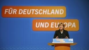 """A chanceler alemã Angela Merkel e líder da União Democrata Cristã (CDU) discursa durante congresso do partido, com o texto """"Pela Alemanha e Europa"""" ao fundo"""