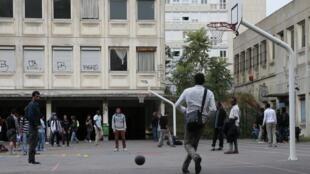 Des migrants jouent au basket-ball dans la cour du lycée transformé en centre d'accueil improvisé à Paris, le 31 juillet 2015.