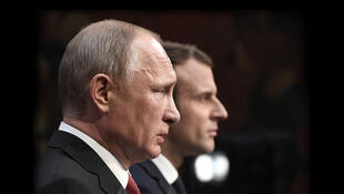 Russian President Vladimir Putin (front) delivers a speech during a joint press conference with French President Emmanuel Macron (rear) in the Galerie des Batailles (Gallery of Battles) following their meeting at the Versailles Palace, near Paris, on May 2