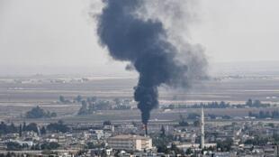 Des flammes s'échappent d'un bâtiment dans la ville syrienne de Ras al Aïn, à la frontière turque, le 18 octobre 2019.