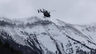 A rescue helicopter from the French gendarmerie flies over the snow covered French Alps near the crash site of Airbus A320 on 25 March 2015