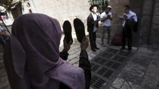 Uma palestina se manifesta diante de judeus que rezam na Esplanada das Mesquitas