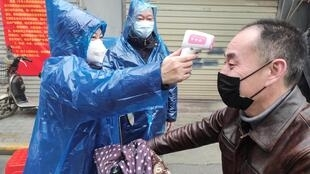 A health worker takes a body temperature measurement of a man at the entrance to a residential compound in Wuhan.