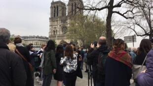 Al día siguiente de la tragedia, parisinos y turistas se concentran frente a la catedral.
