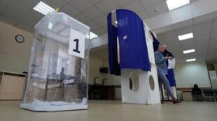 Une femme sort de l'isoloir d'un bureau de vote lors de l'élection du parlement de la ville de Moscou. Moscou, le 8 septembre 2019.