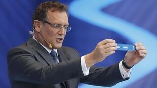 """FIFA Secretary General Jerome Valcke holds up the slip showing """"France"""" during the draw for the 2014 World Cup at the Costa do Sauipe resort in Sao Joao da Mata"""