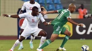 Senegal's Papa Diop Koulygrabs the shirt of Algeria's Yacine Brahimi.