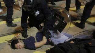 Un policía hongkonés arresta a un manifestante frente a la oficina de enlace con Pékin, el 28 de julio de 2019.