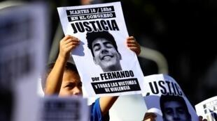 Un enfant tient la photo de Fernando Baez Sosa 18 ans, battu à mort par huit rugbymen devant une discothèque, lors d'une manifestation devant le Congrès national pour exiger que justice soit rendue, le 18 février 2020.