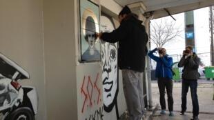 Tinho pinta o muro, observado pelos passantes no Quai d'Austerlitz, em Paris, em 16 de fevereiro de 2013.