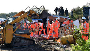 """Workers begin the demolition of the Calais """"Jungle"""" camp, in Calais, northern France, on October 25, 2016 as hundreds of migrants boarded buses on the second day of a massive operation to clear the squalid settlement."""