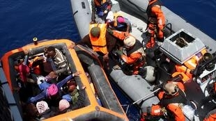 German servicemen assist rescued refugees boarding the frigate Hessen some 130 nautical miles off the Italian Lampedusa island, 8 May 2015