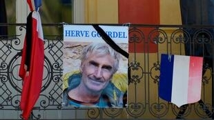 A portrait of mountain guide Frenchman Hervé Gourdel hangs near a French flag outside the town hall in Saint-Martin-Vesubie