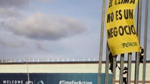 Activistas de Greenpeace colocan una banderola que reza 'El clima no es un negocio', en las afueras de la COP25, este 13 de diciembre de 2019.