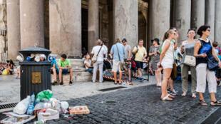 Turistas ao lado de uma lixeira transbordando no centro de Roma.
