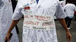 "An emergency services employee wears a medical uniform with a message reading ""Hospitals and patients in absolute emergency"" during a demonstration, 26 September 2019"