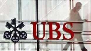 A man walks past a logo of Swiss bank UBS in Zurich