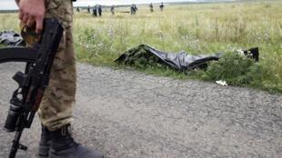 烏克蘭東部,馬航飛機失事現場,遇難者的遺骸邊上站着持槍的分離份子。