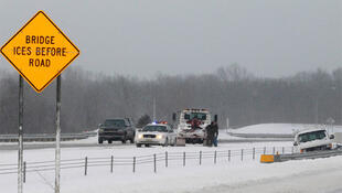 A State Highway Patrol car arrives with a tow truck to assist a van off the road on Interstate 71 in Medina County Ohio