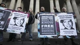 Protesters hold placards in support of Bradley Manning