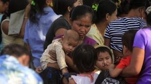 A woman holds her child after fleeing from Myanmar into Thailand