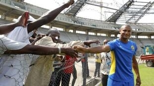 Gabon's striker Daniel Cousin (R) meets construction workers before a training session at the Omnisport Stadium in Libreville