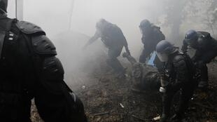 French gendarmes apprehend a protester during clashes in the zoned ZAD (Deferred Development Zone) in Notre-Dame-des-Landes on Sunday