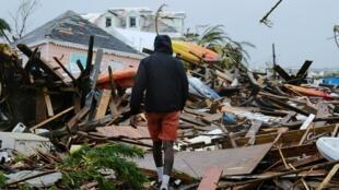 Un homme marche dans les décombres à Marsh Harbour après le passage de l'ouragan Dorian.