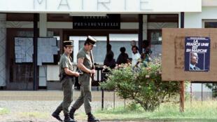 Des gendarmes en patrouille devant la mairie de Poya, le 8 mai 1988, pendant le second tour de la présidentielle française, quelques jours après l'assaut de la grotte de Gossanah à Ouvéa le 5 mai.