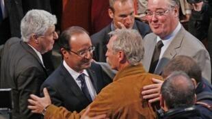 O presidente François Hollande é parabenizado pelo deputado europeu ecologista José Bové após seu discurso na conferência anual sobre o meio ambiente em Paris, nesta sexta-feira.