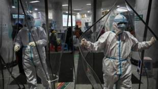 Personal médico con trajes protectores debido al coronavirus, el 25 de enero de 2020 en el hospital de la Cruz Roja en la ciudad china de Wuhan