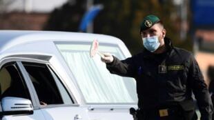 Un carabinier vérifie l'identité d'une conductrice à l'entrée de la ville de Zorlesco au sud-est de Milan, le 24 février 2020