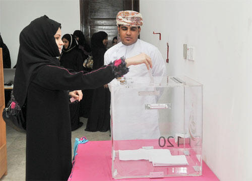 A member of Oman's voting committee casts her vote earlier this week, so as to bre ready to observe Saturday's poll