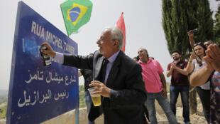 Homem apaga a palavra 'vice' da placa que homenageia Temer em Btaaboura, no Líbano.
