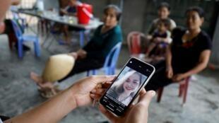 Thân nhân ở Nghệ An xem hình một thiếu nữ Việt Nam bị nghi ngờ là nằm trong số nạn nhân chết trong xe tải tại Anh, 26/10/2019.