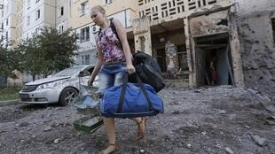 Mulher foge de casa após bombardeio no centro de Donetsk.