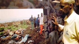 A guide at a memorial to the Rwandan genocide in Kigali looks at photos of victims