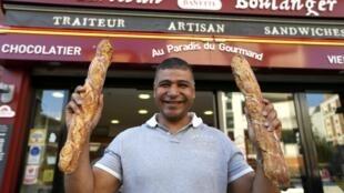 El panadero Ridha Khadher delante de su panadería parisina con dos baguettes.